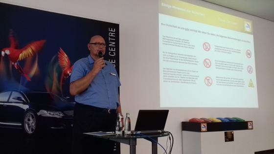 Jürgen Book erklärt Werksbesuchern in Münster die Sicherheitsvorschriften, bevor er über Farben und die Möglichkeiten von Kleinreparaturen mittel Spot Repair referriert. Foto: L. Döhmann